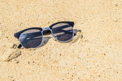 Sunglass on the beach with sand background Stock Photo