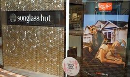 Sunglass förlägga i barack detaljistyttersida med den enorma Ray-Ban annonseringaffischen på skärm Royaltyfri Fotografi