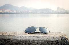 Sunglass and lake side city background. Travel Stock Photography