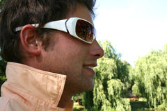 Sunglass Reflection. Young male model with park reflection in sunglasses while standing in the shadow Stock Photos