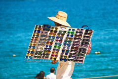 Sunglass Salesman on Beach. Bright sunny day on the beach, local salesman sells tray of colorful sunglasses against the brilliant blue Pacific Stock Images