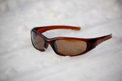 Sunglass on Snow. A dark sun glass on the snow in winter Royalty Free Stock Image