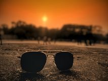 Sunglass and sunset. The sun is bright but the sunglass is brighter than the sun Stock Image