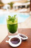 Sunglass and tasty detox cocktail next to swimming pool Royalty Free Stock Photo