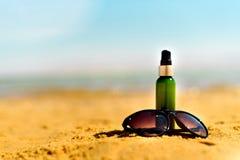 Sunglasse, сливк солнцезащитного крема на желтом пляже песка против предпосылки моря с copyspace Обои каникул и перемещения Стоковые Изображения