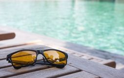 Sunglassed on wood table near swimming pool stock photos