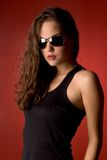 Sunglasses. Attractive brunette, wearing sunglasses, against red background stock photos