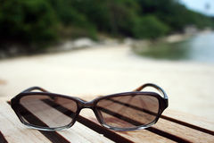 Sunglasses. A pair of sunglasses on a wooden deck at the beach Stock Photo