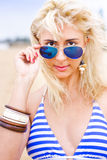 Sunglasses. Close Up Of A Beautiful Blond Woman Modelling A Intense Look Over The Top Of Her Sunglasses In A Cool Outdoor Oceanic Seaside Portrait Stock Photos