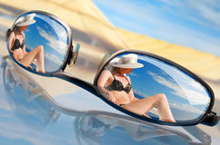 Sunglasses. Reflecting the girl on a deck-chair Royalty Free Stock Images