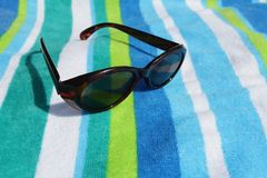 Sunglasses. On a beach towel Stock Image