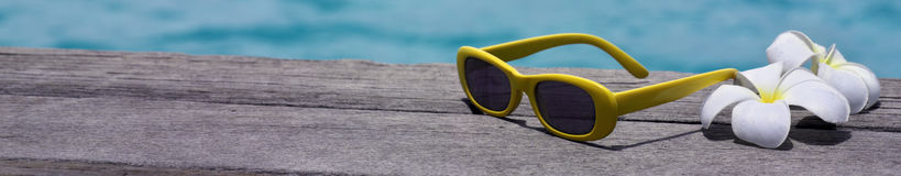 Sunglasses. On the beach with flowers Stock Photo