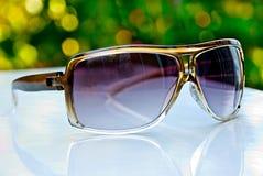 Sunglasses. Dark women's sunglasses on a white desk Royalty Free Stock Photo