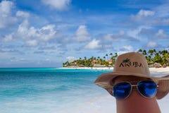Sunglasses and Aruba hat on a leg. Eagle beach on background royalty free stock photos