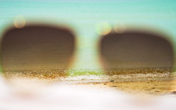 Sunglasses on background of sea and sand Royalty Free Stock Photo