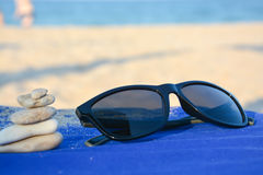 Sunglasses and a balanced pebbles tower on a sunny beach Royalty Free Stock Photography