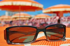 Sunglasses and beach. Closeup of sunglasses and beach with orange umbrellas in background, Rimini, Italy Royalty Free Stock Photo