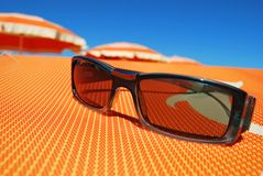 Sunglasses and beach. Closeup of sunglasses and beach with orange umbrellas in background, Rimini, Italy Royalty Free Stock Image