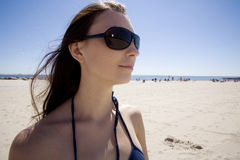 Sunglasses on the beach. A beautiful young brunette woman wears sunglasses on the beach stock images