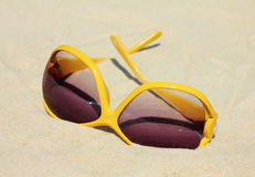 Sunglasses on the beach. Upturned Yellow Sunglasses surrounded by dry sand Stock Photography