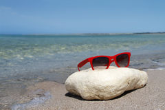 Sunglasses on the beach. Red sunglasses on the beach Stock Photo