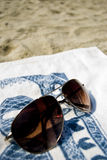 Sunglasses and towel on the beach, holiday concept. Sunglasses on the beach towel royalty free stock photos