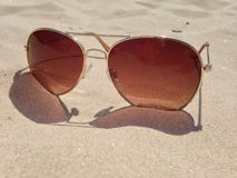 Sunglasses on the beach. Aviator style sunglasses on the beach, in the sand Royalty Free Stock Photo