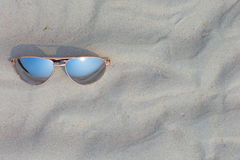 Sunglasses on the beach. Sunglasses lying on the beach, white sand royalty free stock photos