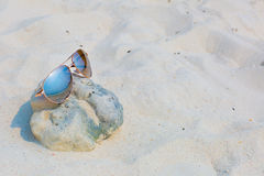 Sunglasses on the beach. Sunglasses lying on the beach, white sand, wave Stock Photography