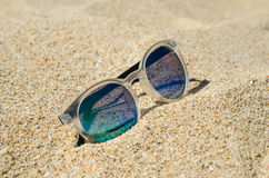Sunglasses on the beach. Multi colored stylish model with transparent frame and blue lenses. Vacation concept. Sunglasses on the beach. Multi colored model with stock images