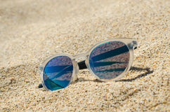 Sunglasses on the beach. Multi colored stylish model with transparent frame and blue lenses. Vacation concept. Sunglasses on the beach. Multi colored model with royalty free stock photo