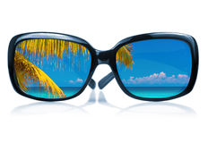 Sunglasses with a beach reflected on the glass Stock Photo