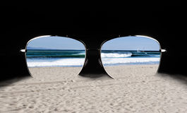 Sunglasses with Beach Reflection. Sunglasses resting on sand with reflection of beach waves and sailboat on the Pacific Ocean stock photos