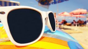 Sunglasses on the beach. Sunglasses on the rubber ball Royalty Free Stock Photo