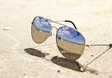 Sunglasses on the beach. Sea landscape reflecting in the sunglasses on the beach Royalty Free Stock Image