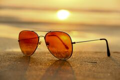 Sunglasses on beach at sunset royalty free stock images