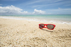 Sunglasses and beach Stock Images