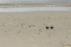 Sunglasses on beach. Travel relax vacation white sand, shining sun Stock Photo