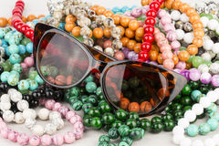 Sunglasses and beads. Royalty Free Stock Photography