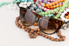 Sunglasses and beads. Royalty Free Stock Photo