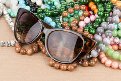 Sunglasses and beads. Royalty Free Stock Images