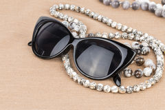 Sunglasses and beads. Stock Photos