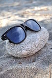 Sunglasses. Black sunglasses on stone, on the beach Stock Photography