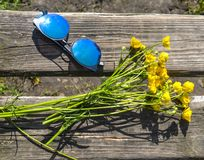Sunglasses with blue glasses next to a bouquet of wild flowers stock photography