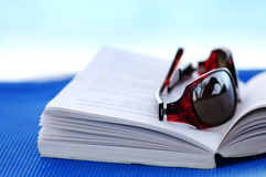 Sunglasses and book on beach chair Royalty Free Stock Images