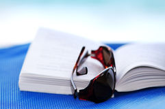 Sunglasses and book on beach chair Stock Photography