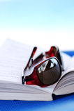 Sunglasses and book on beach chair Royalty Free Stock Photo