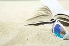 Sunglasses and book on the beach Stock Photos