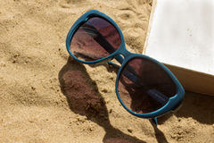 Sunglasses and book over sand Royalty Free Stock Images