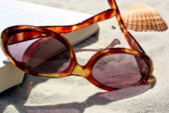 Sunglasses and book on sand. A closeup view of sunglasses and a book on beach sand with a seashell nearby.  Theme:  beach vacation, holiday, summer Royalty Free Stock Photography